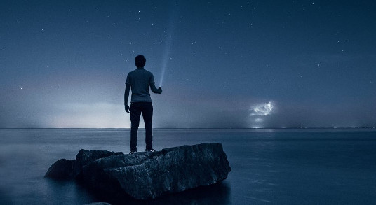 A man with a flashlight looking it over the ocean.